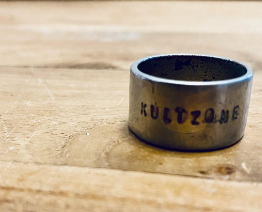 Kultzone - Symbolfoto (Ring mit Kultzone-Gravur auf Holzbrett)